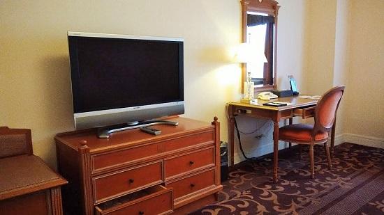 ベッドの向かいに小さめデスクとテレビ