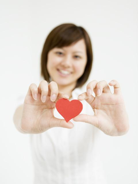 白い服の女性が笑顔で赤いハートのマスコットを差し出す写真