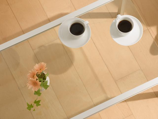 ガラステーブルに小さな花と2人分のコーヒー