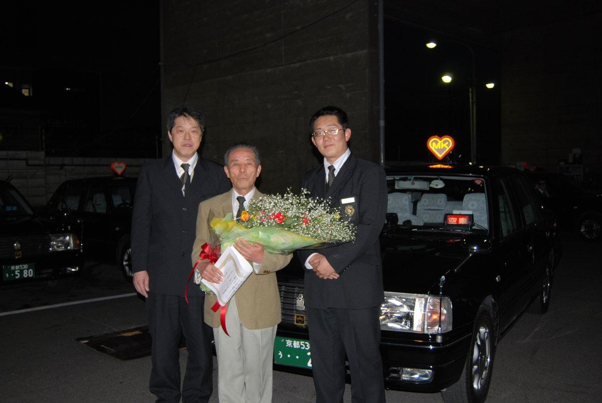 伏見営業所長(右)、及び同僚社員(左)と、タクシー車両の前で MK新聞2018年5月1日号より