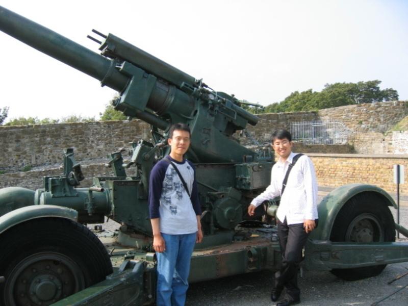 砲台の前で柴田社員と MK新聞2006年10月1日号より(右が北野社員)
