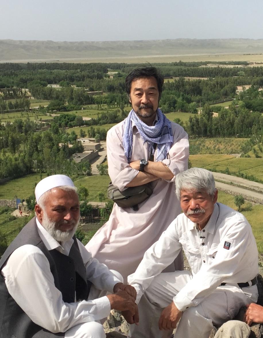 ガンベリ農場を望む丘の上で。中村医師、パチャグル氏とともに(中央が谷津さん)