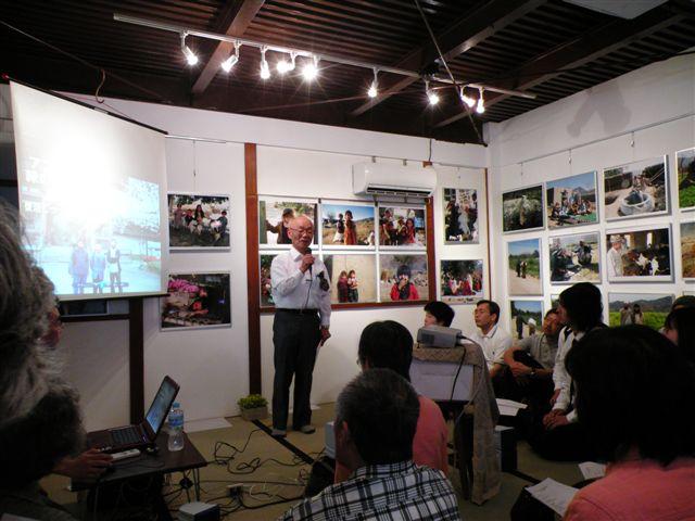 伊藤和也さん撮影の写真に囲まれて講演する高橋さん