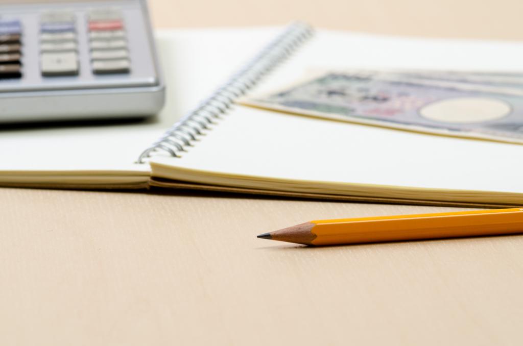 電卓と鉛筆とノートとお札