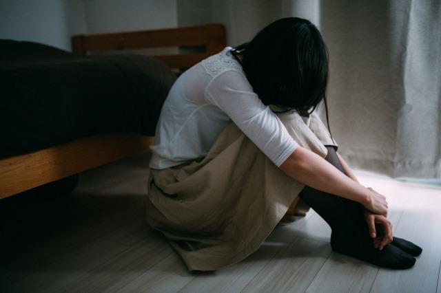 部屋で膝を抱えてうずくまる女性