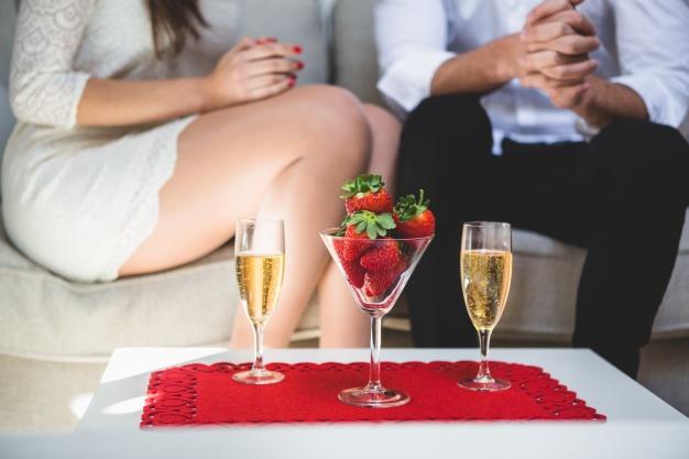シャンパンと苺を前にソファに座る男女