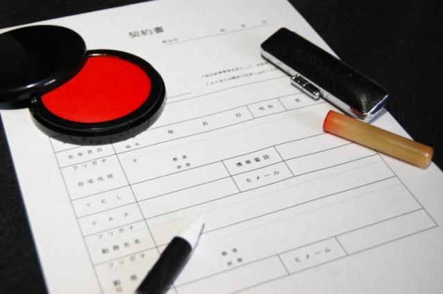 契約書の上の印鑑と朱肉とボールペン