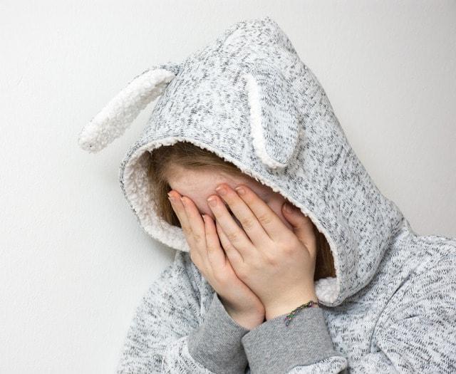 耳付きフードを被って手で顔を覆っている女の子