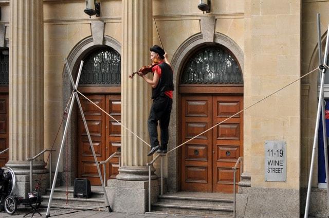バイオリンを弾きながら綱渡りをするピエロ