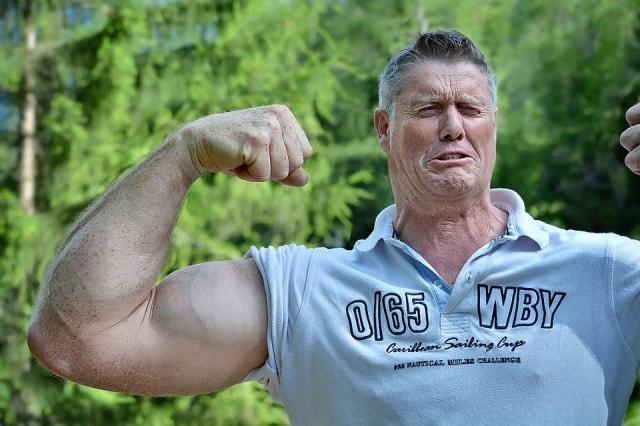腕の筋肉を見せつけるおじいさん
