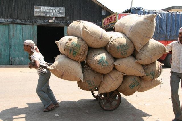 たくさんの袋が載ったリヤカーを引く男性