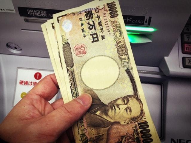 ATMの前で一万円札を持っている手