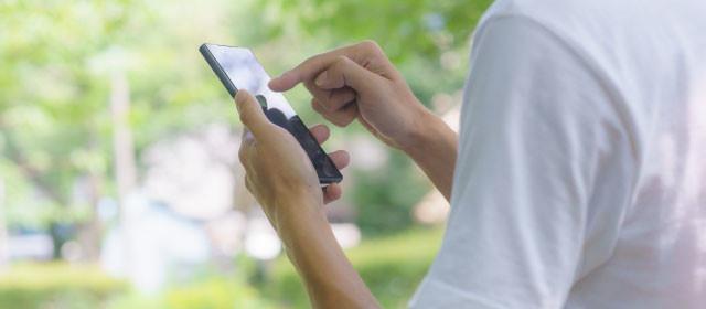 海外で携帯電話を使う人の写真