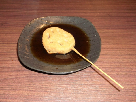 東京都練馬区田柄5丁目にある串焼き・串揚げ、居酒屋のお店「前田屋商店」小皿に入れた串かつソースにレンコンを浸した様子