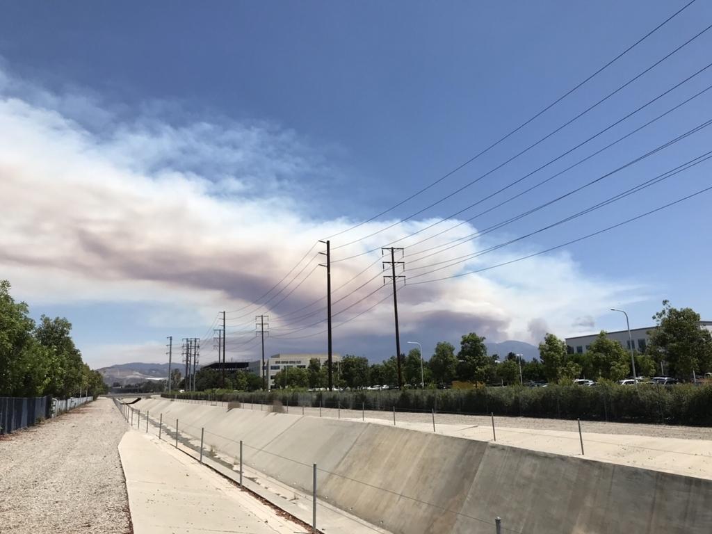 遠くの山火事の煙が流れている空と乾いた水路