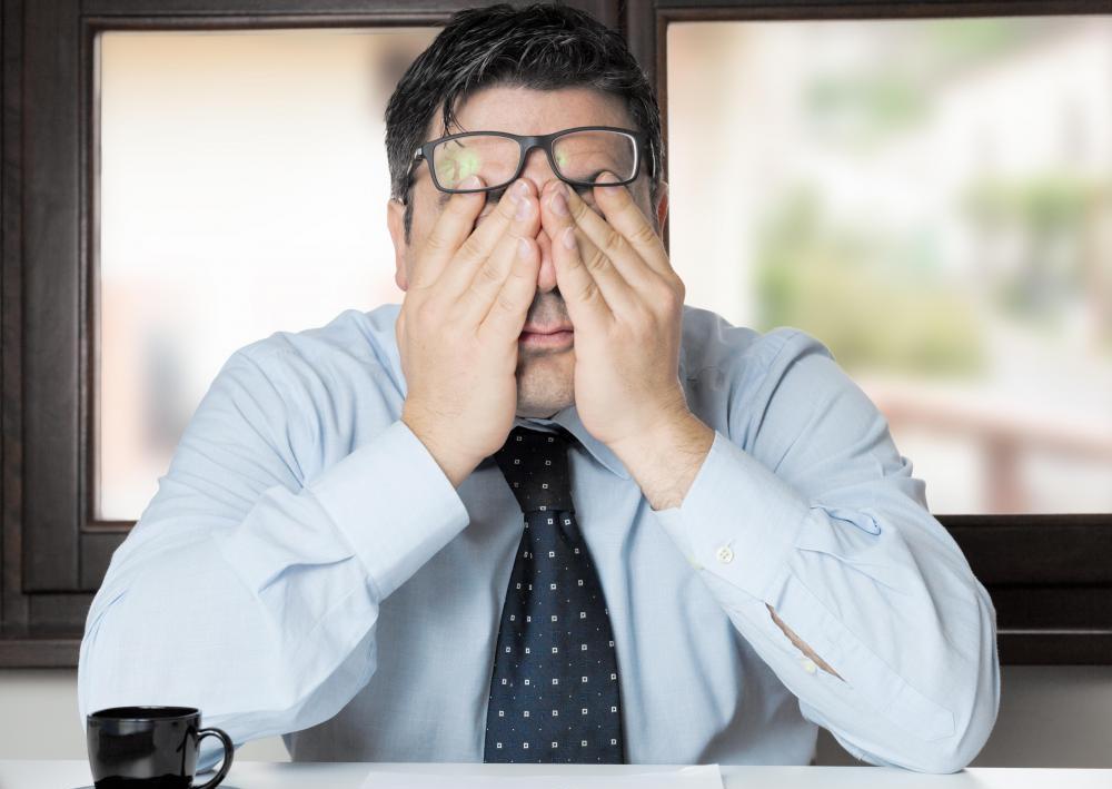 眼精疲労でイライラとストレスを感じているビジネスマン
