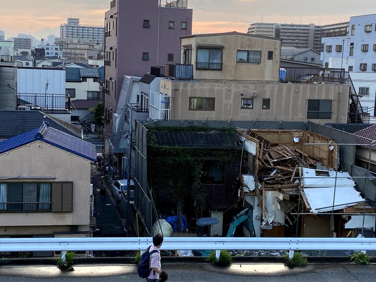 夕暮れ時、解体途中の家の風景を撮影した写真