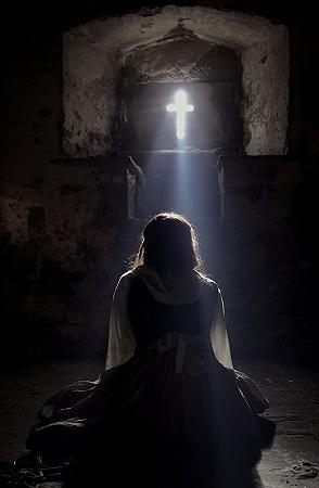 十字架に祈るシスター