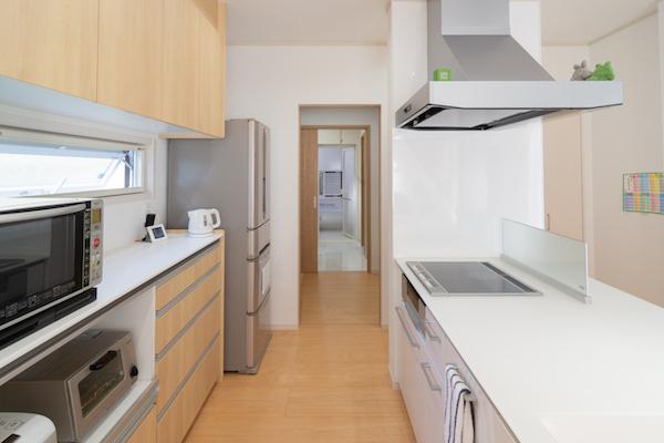 キッチンから家事室、洗面室、浴室が一列に並んだ、家事動線抜群の間取り。キッチンを回遊型にし、通路幅を広く取ったのは、「将来、娘たちや両親と一緒に使うことになっても利用しやすいように」との妻のこだわり(写真/島崎耕一)