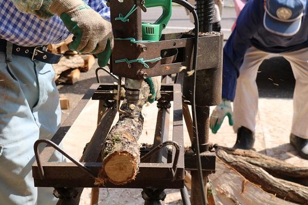 原木に電動ドリルで穴をあける