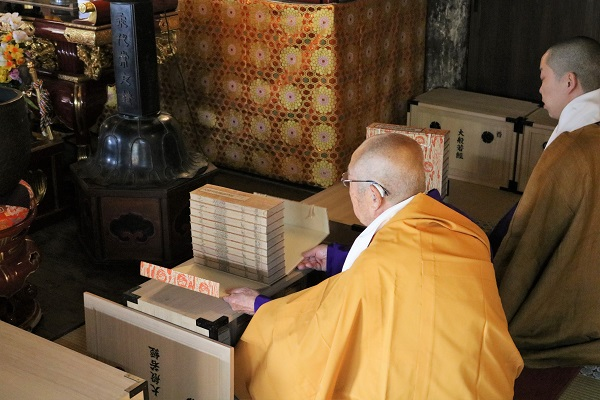 木箱から経典を取り出す僧侶