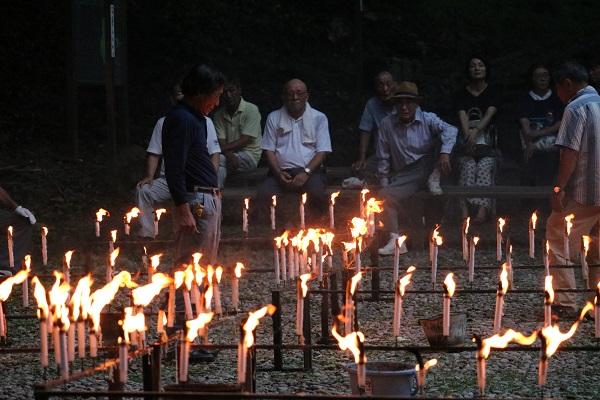 千灯供養のローソクの炎を見つめる参拝客