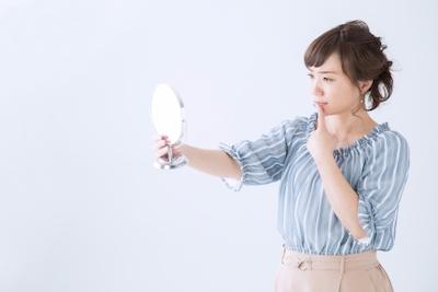 口元を鏡で見る女性