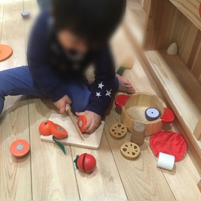 木製のおままごとコーナーで遊ぶ2歳