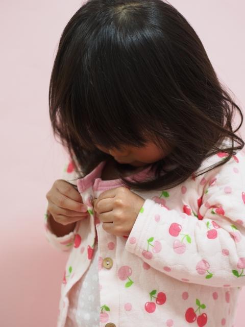 パジャマのボタンをつける子供