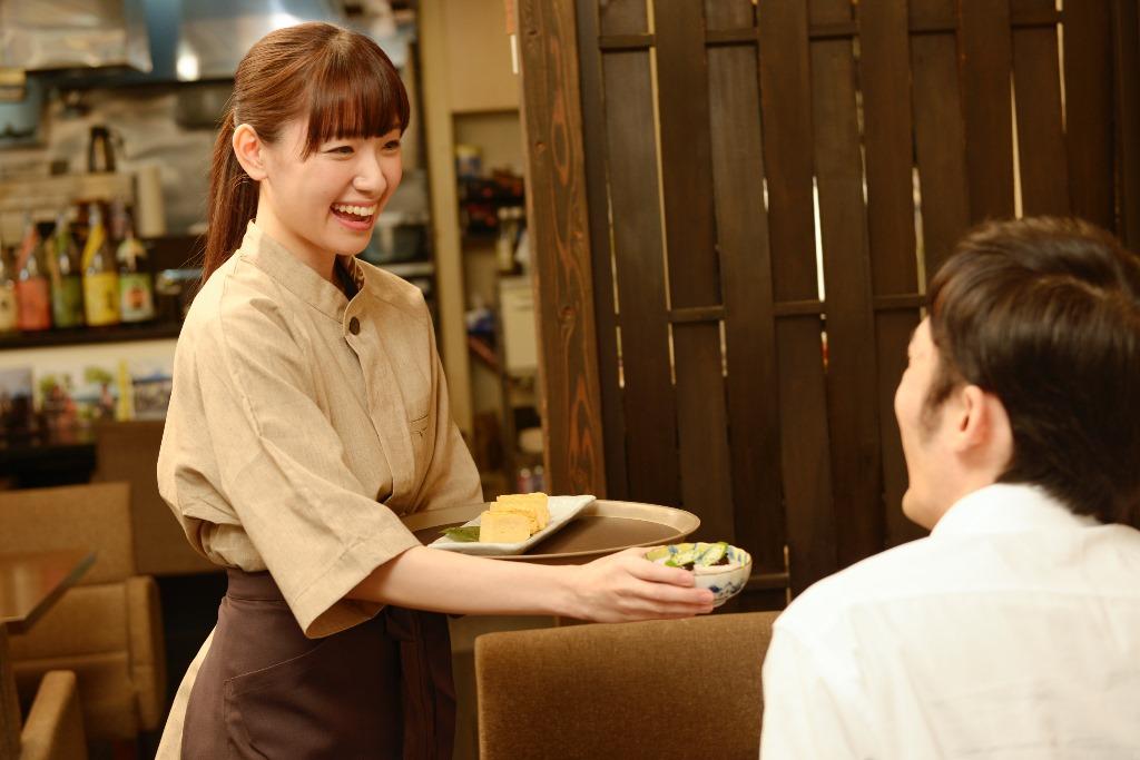 笑顔で接客する飲食店で働く人