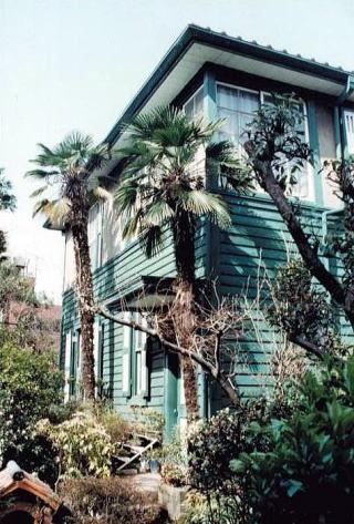 緑色の板壁と白の窓枠の美しい西片邸