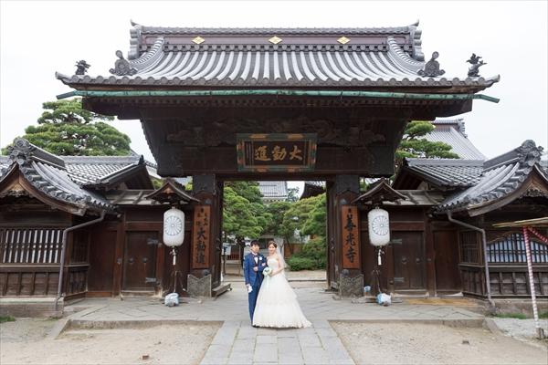 善光寺大勧進の門に立つ新郎新婦