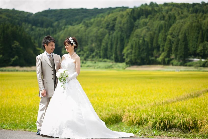 田んぼの脇に立って撮影するタキシードとドレスの新郎と新婦