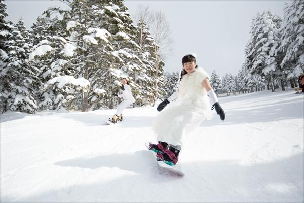 ゲレンデをドレスで滑る新婦の画像