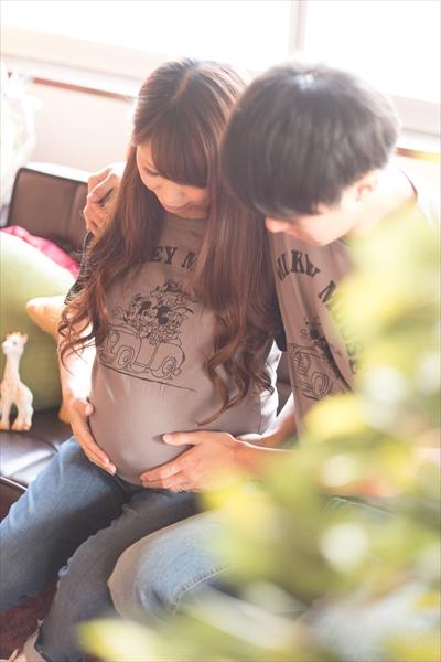 妊婦の妻のお腹を見る夫婦の画像