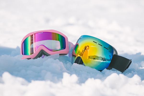スキーゴーグルに写ったタキシードとドレスの新郎と新婦
