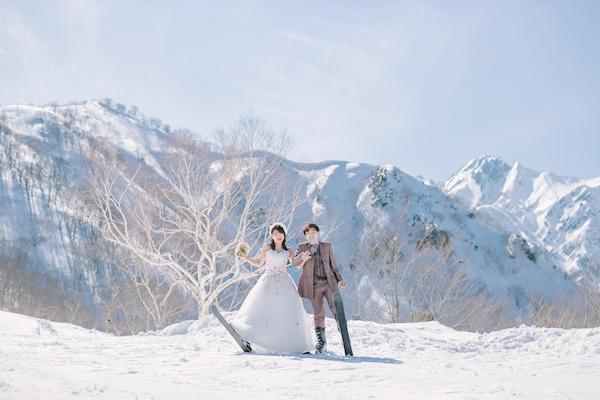 スキー場でタキシードとドレスで撮影する男性と女性