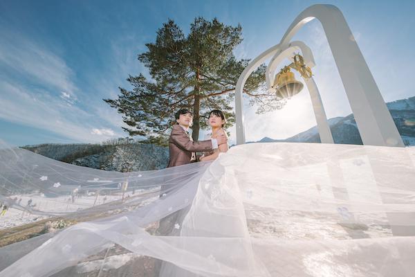 スキー場にてタキシードとドレスで撮影する男性と女性
