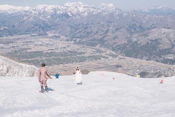 ゲレンデをタキシードとドレスで滑る男性と女性