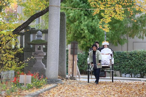 紋付袴と白無垢で人力車に乗っている新郎と新婦