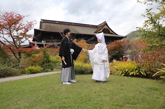 善光寺をバックに撮影する新郎と新婦
