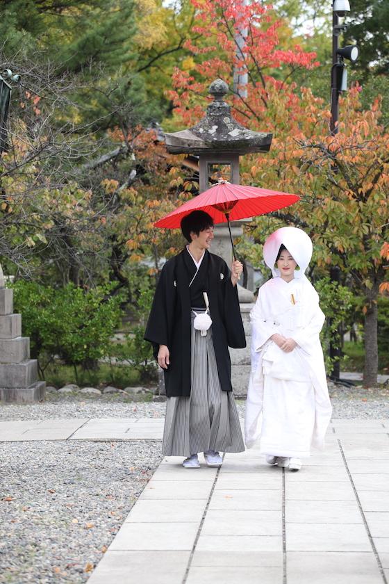 善光寺の境内を紋付袴と白無垢で歩く新郎と新婦