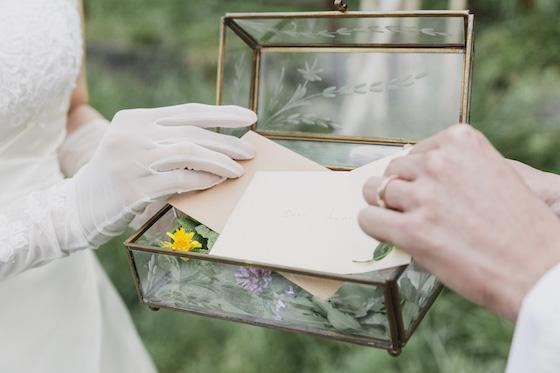 タキシードの男性とドレスの女性が手紙を箱に入れる画像