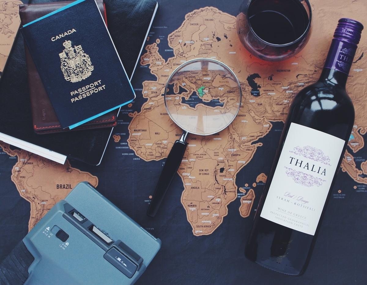 デスク上のワインや虫眼鏡、パスポート