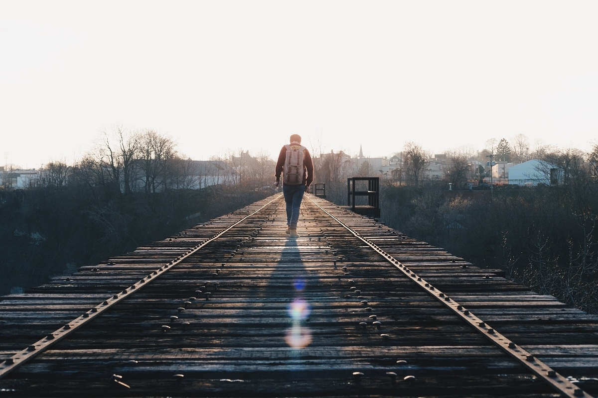 線路を背を向けて歩く男性