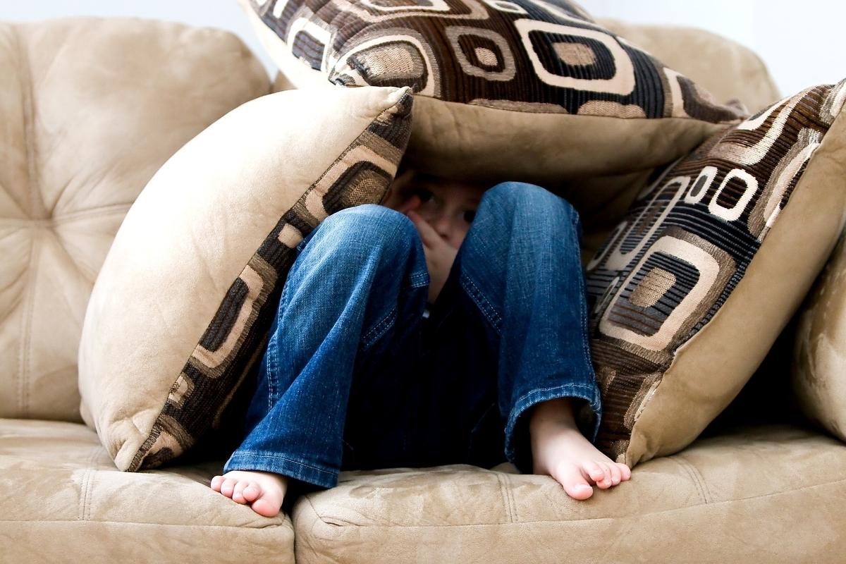 ソファに座りクッションで体を覆う人