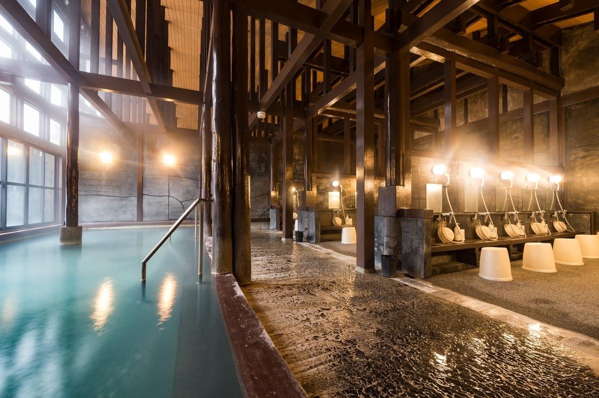 硫黄の匂いが漂う青白く濁った源泉かけ流しの大浴場「ひらゆの森」の内湯
