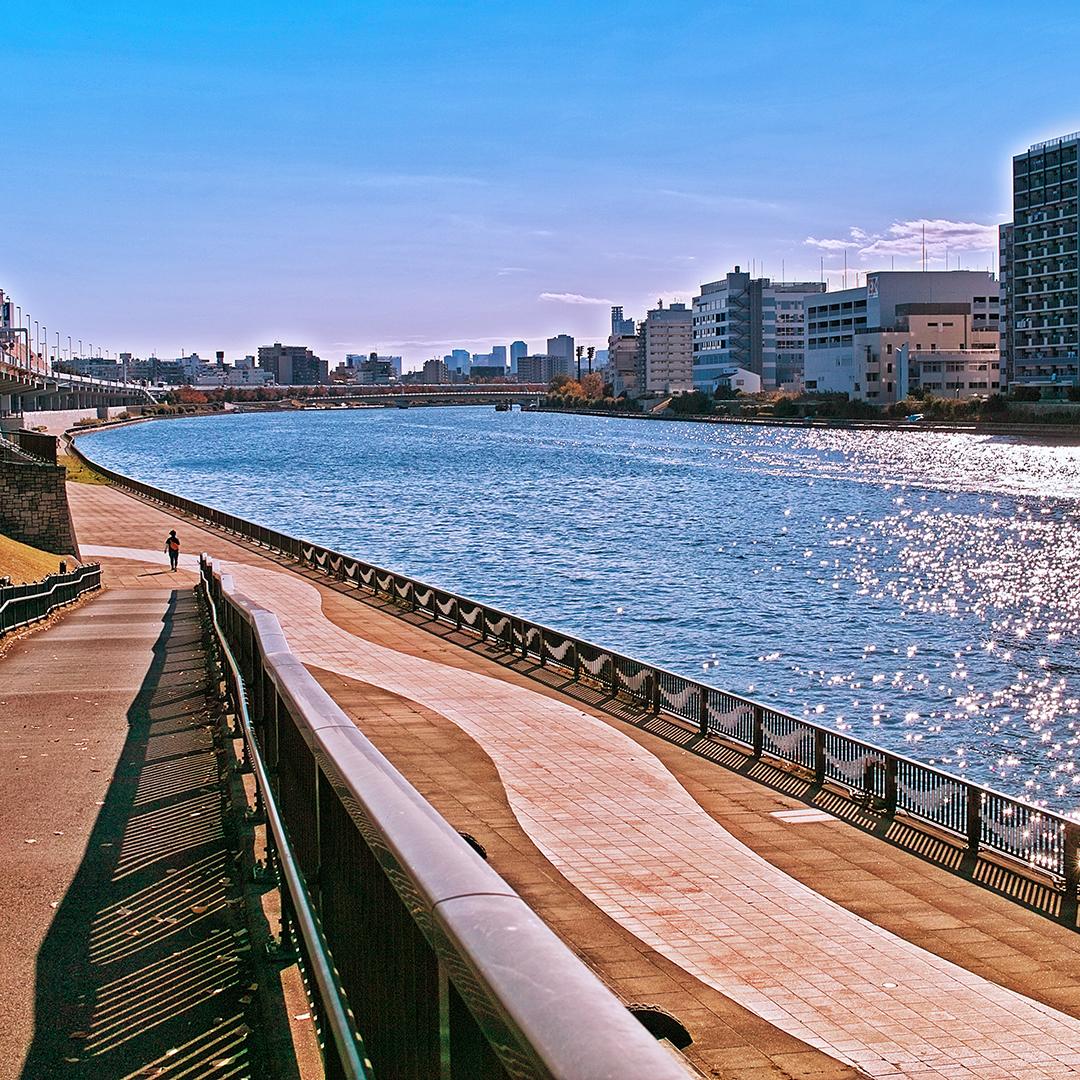 よく晴れた秋の日の隅田川と隅田川沿いの歩道