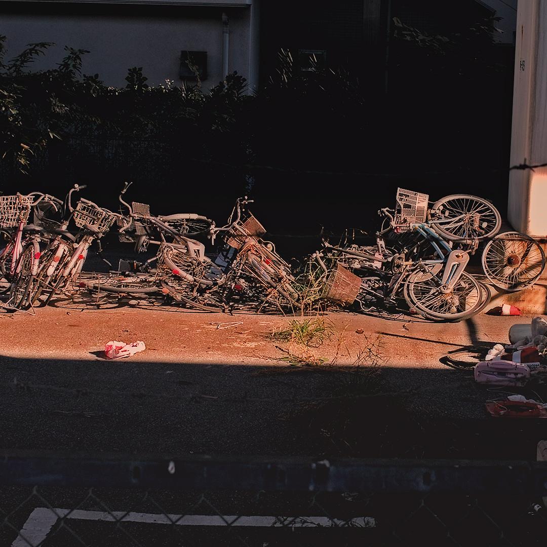自転車が乱雑に捨てられるように並べられている