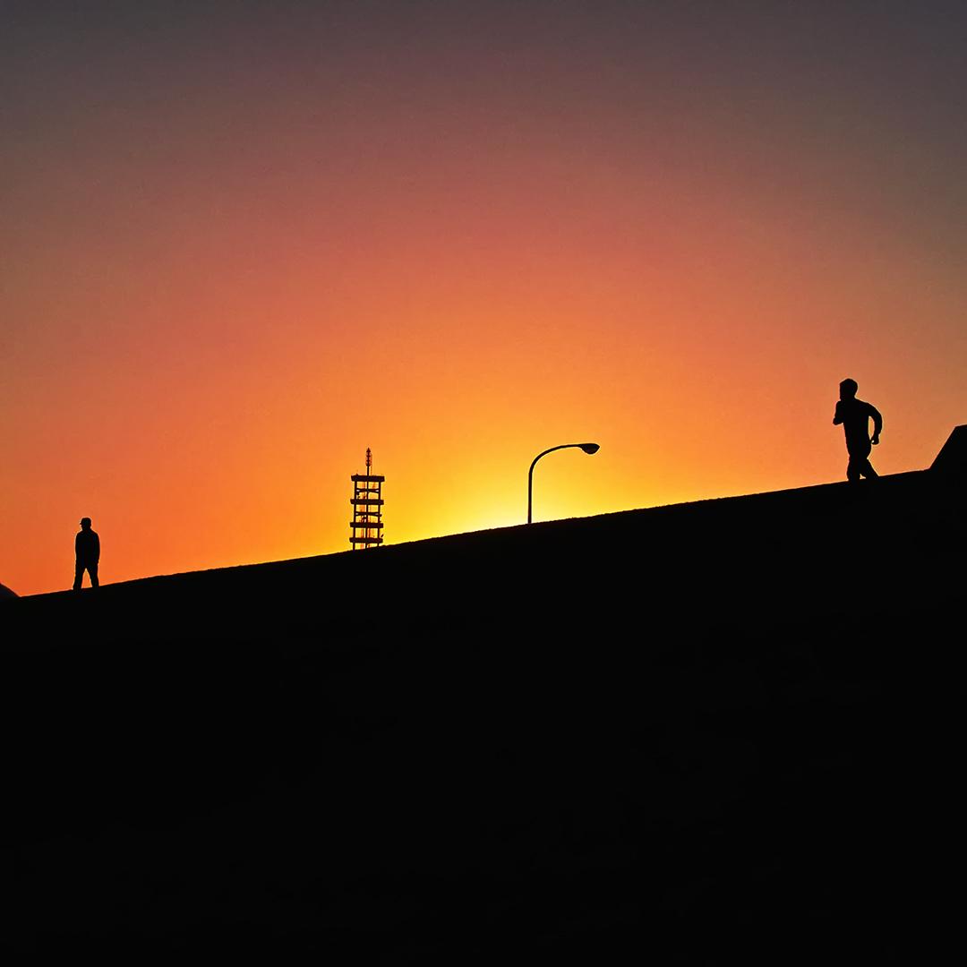 沈む夕陽を背景に逆光で撮った写真で、辺り一面は茜色というよりは蜜柑色に染まり、その色の中に、土手の上を走る人と佇む人と街灯と鉄塔が影絵のように写っている。